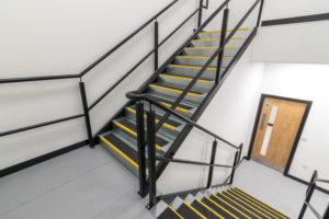 Mezzanine stairwell with safety tread, handrail and solid wood fire door.