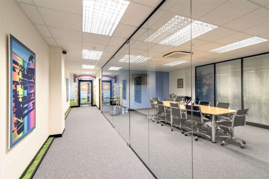 Meeting room with glass partition wall and two full height glass doors & black framework.