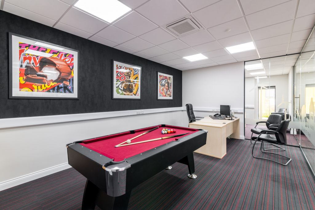 Private office design including feature pool table and statement artwork.